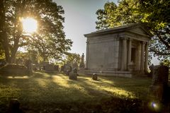Grave Markers at an Old Cemetery. Grave markers and headstones, monuments and trees stand in the late afternoon light in an old Cemetery in Rochester, New York Royalty Free Stock Images