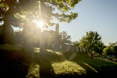 Grave Markers at an Old Cemetery. Grave markers and headstones, monuments and trees stand in the late afternoon light in an old Cemetery in Rochester, New York Stock Photography