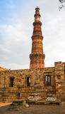 Grave markers with Qutub minar in back. Grave markers with a stone wall and the qutub minar at the back. Shows the rear compound of the Minar Royalty Free Stock Photo