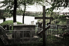 Grave is near the river with a cross. Grave with a cross near the river, on the mountain Royalty Free Stock Image