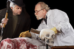 Grave robber and evil doctor exchange glance Royalty Free Stock Image