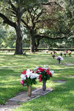 Grave Site. A grave site marked with flowers sits in a shaded grove stock photo