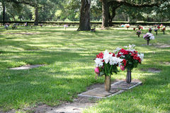 Grave Site. A grave site marked with flowers sits in a shaded grove of trees stock photo