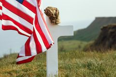 The grave of a soldier. American flag over the grave of the deceased soldier. At the grave a military cap.  royalty free stock photo