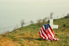 The grave of a soldier. American flag over the grave of the deceased soldier. At the grave a military cap.  stock image