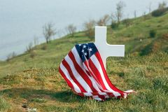 The grave of a soldier. American flag over the grave of the deceased soldier. At the grave a military cap.  royalty free stock image