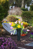 Grave with spring flowers. Spring flowers at cemetery in Germany. Grave with easter decoration. Shallow DOF, focus on flower pot Stock Images