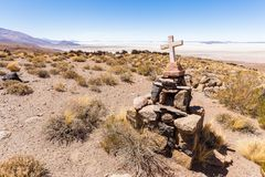 Grave stone cross tomb mountain Salar De Uyuni Bolivia. Tombstone old ancient cross grave archaeology site stone, mountains Salar de Uyuni salt desert view Royalty Free Stock Photography