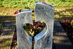 Grave stone with heart and withered rose Stock Image