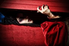 Grave vampire. Bloodthirsty female vampire rises from the coffin on the night cemetery stock photography