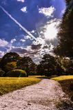 Grave way under a blue sky and some clouds, a really sunny day royalty free stock photos