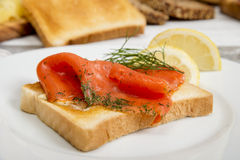 Graved salmon on toast bread with dill and lemon Royalty Free Stock Photography