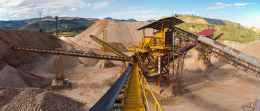 Gravel Aggregate Extraction -. Panoramic gravel pit in mountain area with machinery and distribution tapes gravel according sizes, lots of gravel and sand for Stock Images