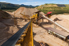 Gravel Aggregate Extraction. Gravel pit in mountain area with machinery and distribution tapes gravel according sizes, lots of gravel and sand for construction Royalty Free Stock Image