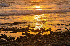 Gravel beach in amber sunlight. Royalty Free Stock Photos