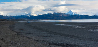 Gravel beach with buildings in the distance Stock Photos