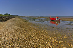 Gravel beach with fishing boat and tidal mudflats Stock Images