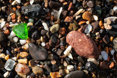Gravel on a beach with a green glass fragment. Gravel on a beach with a bright green glass fragment Royalty Free Stock Photo