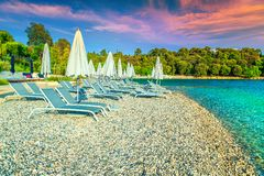 Gravel beach with sun loungers and beach umbrellas at sunset. Beautiful travel and vacation destination. Picturesque gravel beach and seashore. Sun loungers and royalty free stock photo