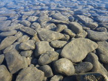 Gravel in a clear mountain lake Stock Photos