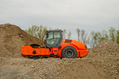 Gravel compactor on pile of gravel.  Royalty Free Stock Images
