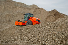 Gravel compactor on pile of gravel.  Stock Photo