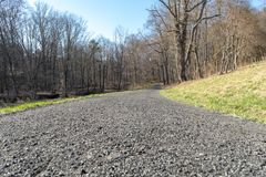 Gravel covered path leading into the distance, into a leafless forrest, on a sunny day royalty free stock images
