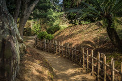 Gravel footpath in the Ritsurin Koen-Chestnut Grove Garden between bamboo fences Royalty Free Stock Images