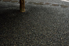 Gravel Garden. Raked gravel surrounding steppingstones and a tree trunk in a small Japanese garden Stock Photos