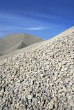 Gravel gray mound quarry stock blue sky. Rolling stones Stock Image