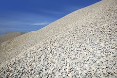 Gravel gray mound quarry stock blue sky. Rolling stones Royalty Free Stock Images