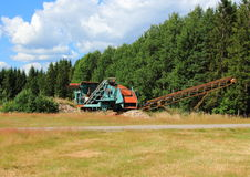 Gravel machine in forest with sky and clouds Stock Images