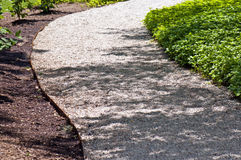 Gravel path. A view of a wide white gravel pathway with landscaping Royalty Free Stock Photos