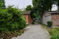 Gravel path in dilapidated red brick buildings Stock Photos