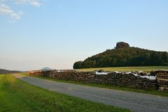Gravel path with wood between field of German landscape with rock castle Zirkelstein on background in Saxon Switzerland at summer. Sunset in June 2018 Stock Images