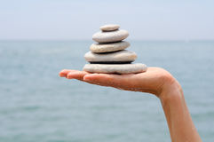 Gravel pile in woman's hands with sea background Royalty Free Stock Photos