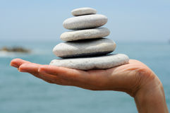 Gravel pile in woman's hands with sea background Stock Photography