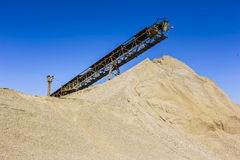 Gravel pit. With an industrial gravel sorter machinery and clear blue sky Stock Photos