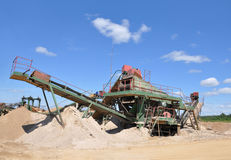 Gravel pits. Crushing machine with conveyor in his career. Production of gravel royalty free stock images