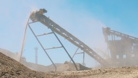 Gravel is pouring from the duct of an industrial machine. 4K stock video footage