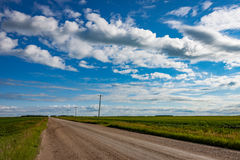 Gravel Road Across Prairie Under Blue Cloudy Sky. Gravel Road Across Canadian Prairie Under Blue Cloudy Sky Royalty Free Stock Photo