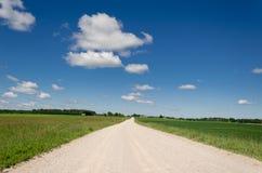 Gravel road along grass blue cloud horizon Stock Photos