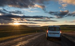 Gravel road along the valley at sunset with lonely car. Car travel in Iceland royalty free stock image