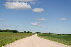 Gravel road continues along  fields and blue sky Stock Images