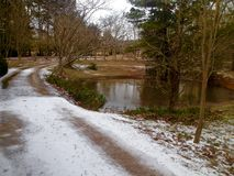Gravel road covered in snow next to a pond Royalty Free Stock Photo