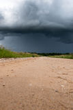 Gravel road and dark clouds. Royalty Free Stock Photo