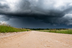 Gravel road and dark clouds. Royalty Free Stock Image