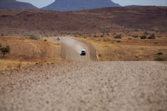 Gravel road in the desert with a car driving Royalty Free Stock Images