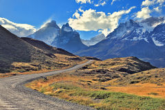 The gravel road  go to the snow-covered mountains Royalty Free Stock Image