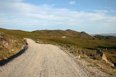 Gravel road through the grassy foothills Royalty Free Stock Photography